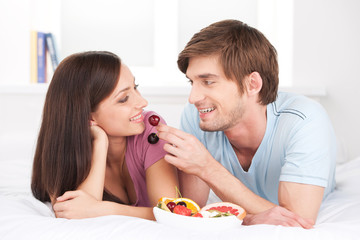 beautiful couple lying in bed and eating.