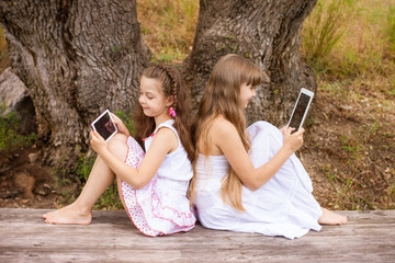 two beautiful girls, sisters with tablets on the street