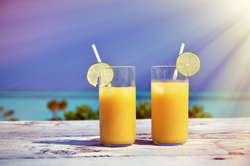 Two glasses of orange juice on the sandy beach