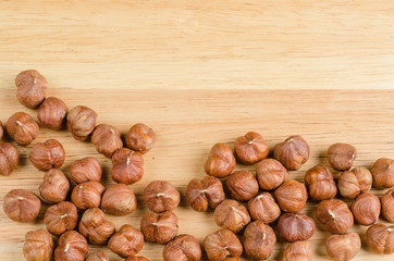toasted hazelnuts without shells, on wood, background