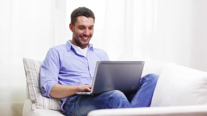 smiling man working with laptop at home