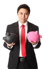 Attractive businessman with piggybanks