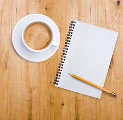 Kaffeetasse und Notizblock auf Holz
