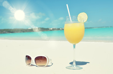 Orange juice and sunglasses on the beach. Exuma, Bahamas