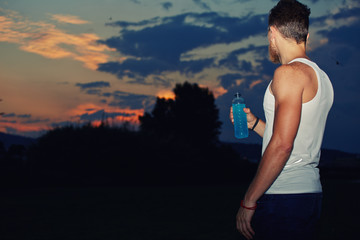 Athletic runner looking to the perfect sunset sky after jog