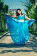 Beautiful woman dancing barefoot in a long blue dress