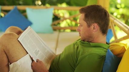 Man reading newspaper in the garden, steadycam shot