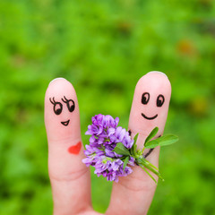 Happy couple. Man is giving flowers to a woman. Finger smileys.