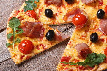 Pieces of pizza with prosciutto, arugula and tomatoes close-up