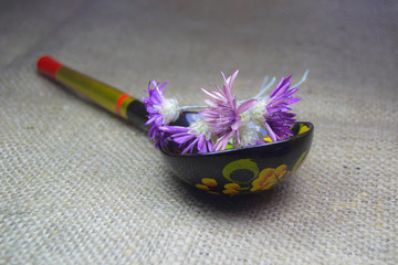 Small bouquet of wildflowers in a wooden spoon on sacking