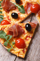 pizza with prosciutto, tomatoes and arugula, olives closeup