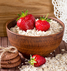 Oatmeal with strawberries in the bowl and cookies