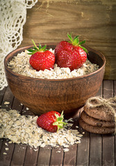 Oatmeal with strawberries in the bowl and cookies.