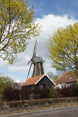 Wooden wind mill in a farm scenery