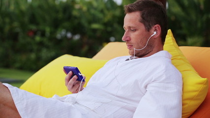 Man watching film on smartphone and lying on bed in the evening