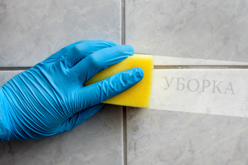 Sponge cleaning bathroom with russian lettering