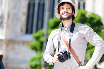 Smiling turist holding his camera