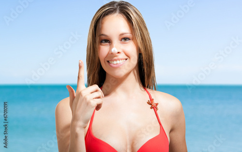 Smiling woman applying sunscreen on the beach