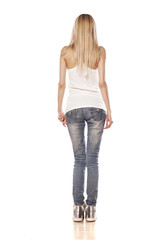 rear view of skinny blonde girl standing on white background