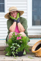 Attractive senior woman potting up plants