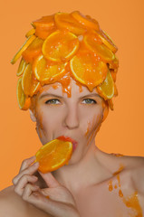 Woman in hat eats slice of orange