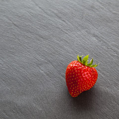 One single ripe red strawberry on slate, with text / copy space.
