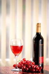 Red vine in glass, grapes and bottle of vine.
