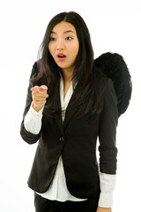 Shocked Asian young businesswoman dressed up as black angel