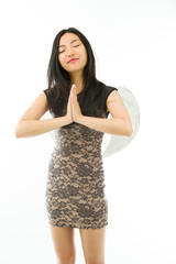 Asian young woman dressed up as an angel in prayer position