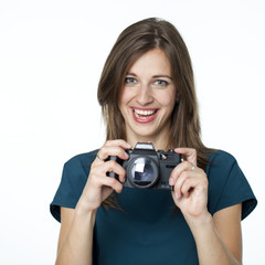 Happy young woman using a camera to take photo
