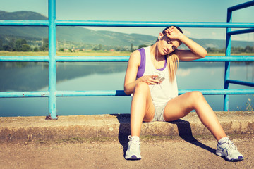 Tired young runner woman with smart phone and headphones
