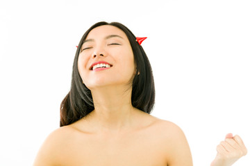 Devil side of a young naked Asian woman celebrating success with
