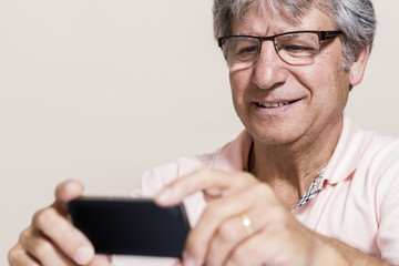 Smartphone and senior man at home