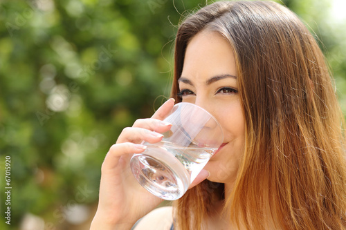 Leinwandbild Motiv Happy woman drinking water from a glass outdoor