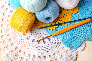 Colorful clews, napkin and crochet hooks on wooden background