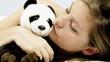 Woman kissing panda plush in bed