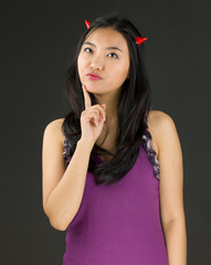 Devil side of a young Asian woman thinking with finger on chin