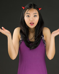 Devil side of a young Asian woman shrugging and looking confused