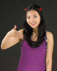 Devil side of a young Asian woman offering hand for handshake