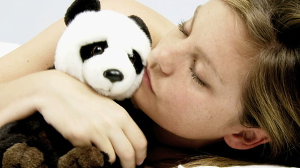 Woman kissing panda plush in bed