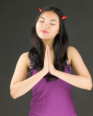 Devil side of a young Asian woman standing in prayer position