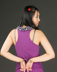 Rear view of devil side of a young Asian woman with handcuffs