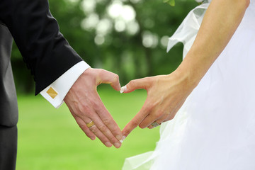 Bride and groom standing together and holding hands in shape of