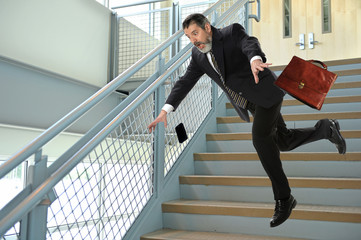 Senior Businessman Falling on Stairs