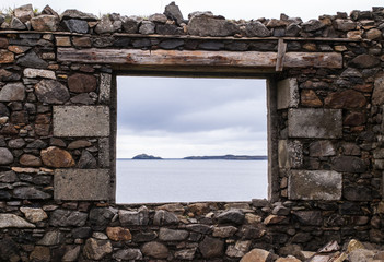 Sea view from a stone window of an old ruin near the ocean