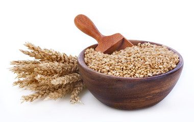 Ripe wheat in a wooden bowl on white background