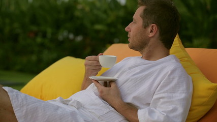 Man drinking coffee and resting in bed
