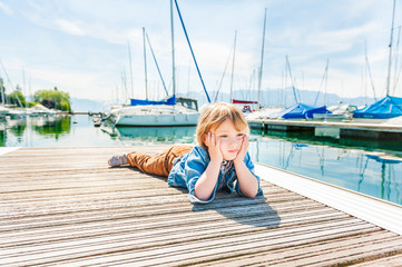 Sad toddler boy laying on a pier