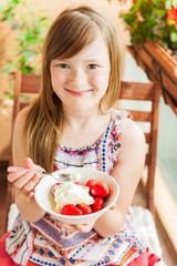 Cute little girl eating strawberry with ice cream