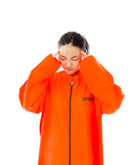 Young Asian woman suffering from headache in prisoners uniform